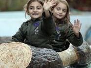 """Die Komani-Zwillinge winken von der Wasserbahn im Wiener Prater. Der Rechtshilfe-Verein """"Purple Sheep"""" organisierte den Besuch."""