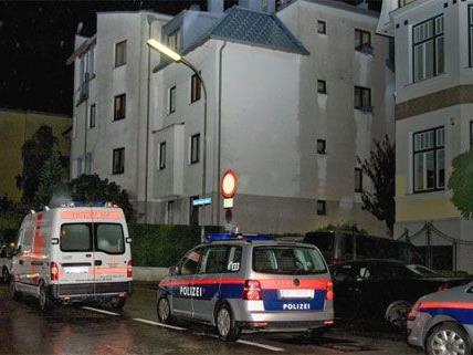 Einsatzfahrzeuge der Polizei und der Rettung vor dem Haus in dem der Mord und Selbstord geschehen sein soll.