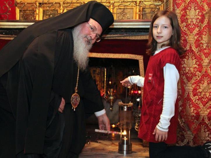 Die 11-jährige Sarah Schinwald aus Munderfing im Bezirk Braunau übernahm am Montag, 21. November 2011, in der Geburtsgrotte in Bethlehem das Friedenslicht vom griechisch-orthodoxen Bischo Theofilaktos (r.).