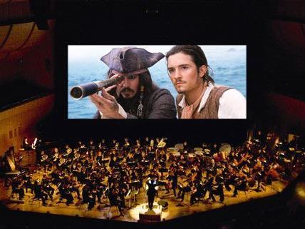 """Orlando Bloom und Johnny Depp kämpfen in """"Fluch der Karibik"""" auf der Leinwand, ein 90-köpfiges Orchester spielt live auf der Bühne."""