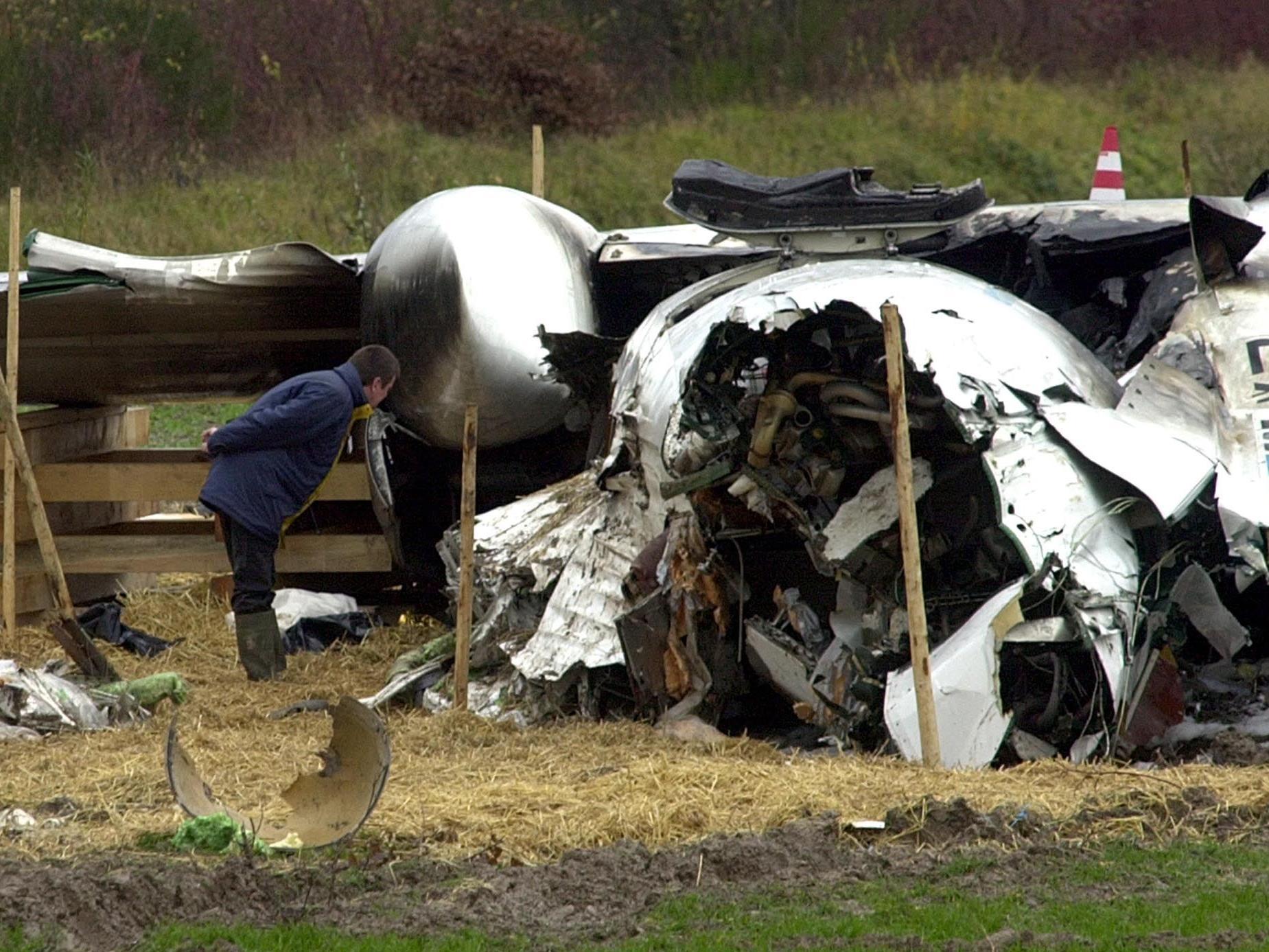 Ein Ermittler betrachtet das Wrack der abgestuerzten Lux Airmaschine in Niederanven in Luxemburg.