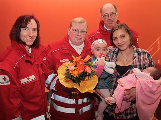 Die drei Rotkreuz-Sanitäter Maike Ratzke, Andreas Hartl, Erwin Batik mit der großen Schwester Vanesa, Mutter Besarta Maloku und der neugeborenen Loressa (v.l.n.r. )