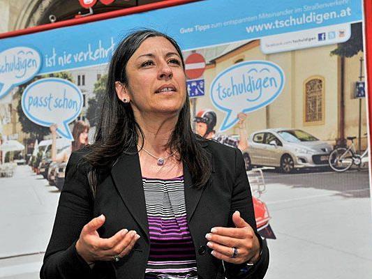 """Vizebürgermeisterin Maria Vassilakou vor einem Plakat für """"tschuldigen"""", die Kampagne für mehr Rücksicht im Straßenverkehr"""