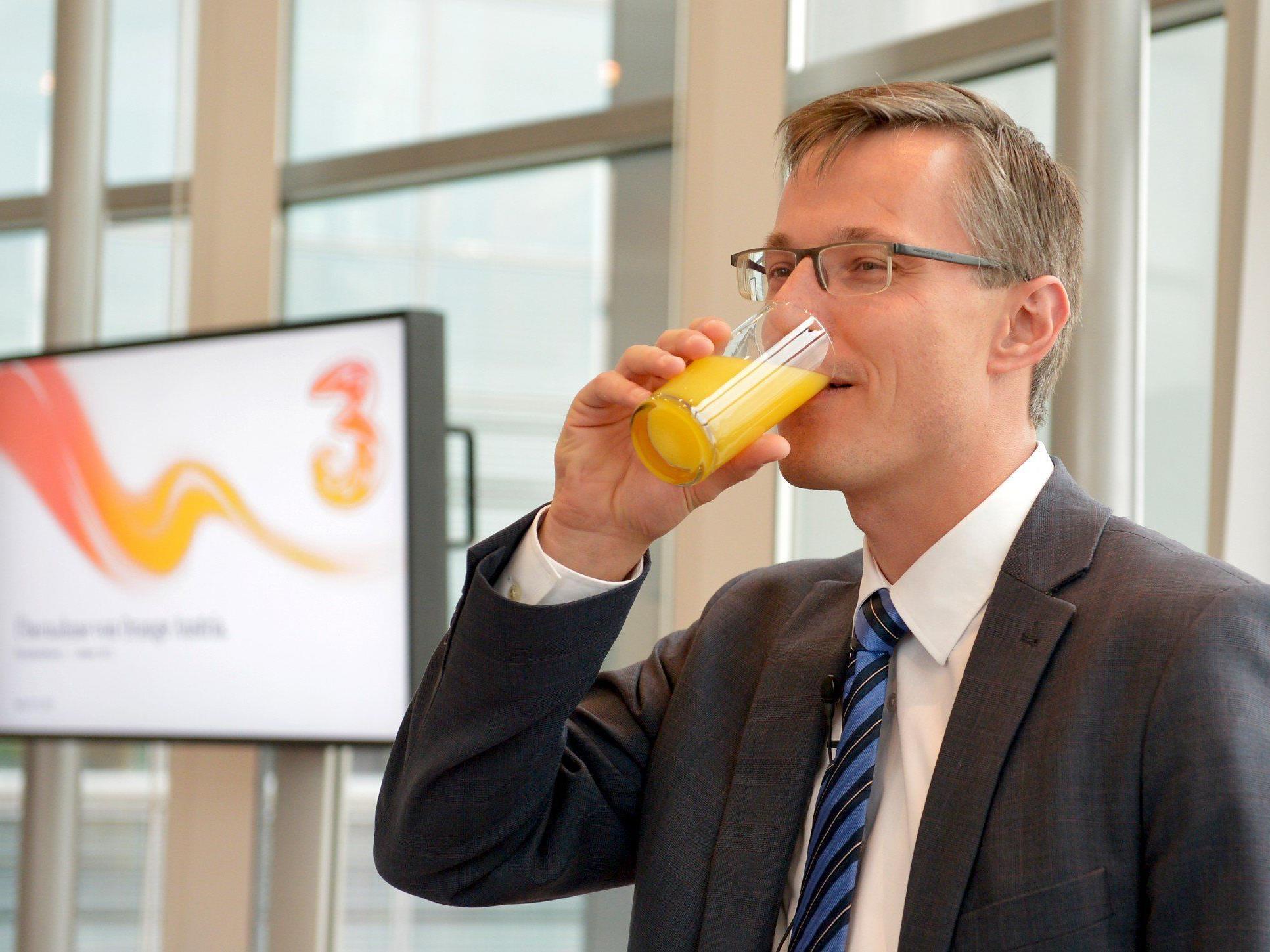 """""""Drei""""-CEO Jan Trionow mit einem Glas Orangensaft bei einer Pressekonferenz zur Übernahme."""