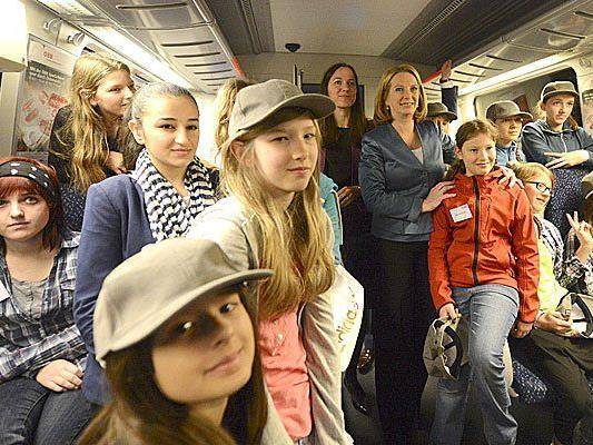 """Verkehrsministerin Doris Bures (mitte rechts) und Birgit Wagner (mitte links, Vorstand ÖBB Personenverkehr) mit Mädchen des Aktionstages """"Girls Day"""" während einer Fahrt in einem Zug"""