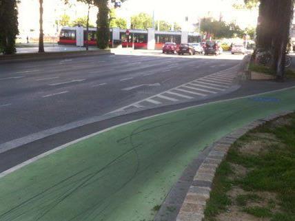 Auf den grünen Radwegen sind schwarze Spuren sichtbar.
