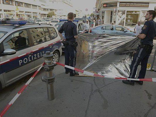 Polizisten schützen den Tatort in Simmering vor neugierigen Blicken