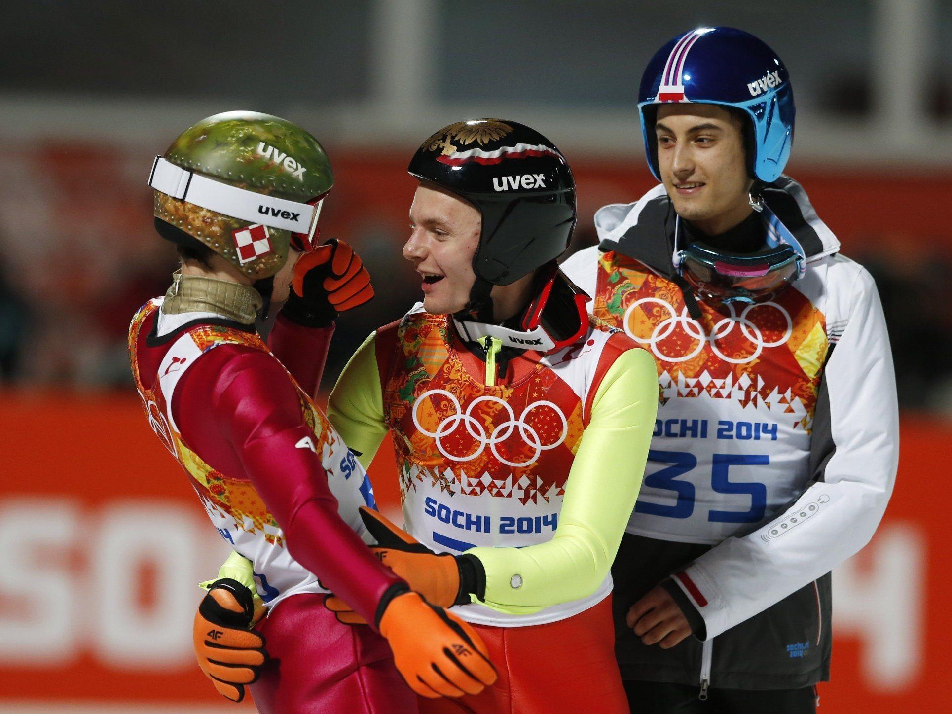 Kamil Stoch (im Bild mit deinen Teamkollegen) gewinnt die Goldmedaille auf der Normalschanze.