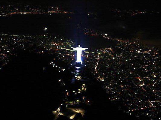 Christus-Statue blickt auf wenig illuminiertes Rio