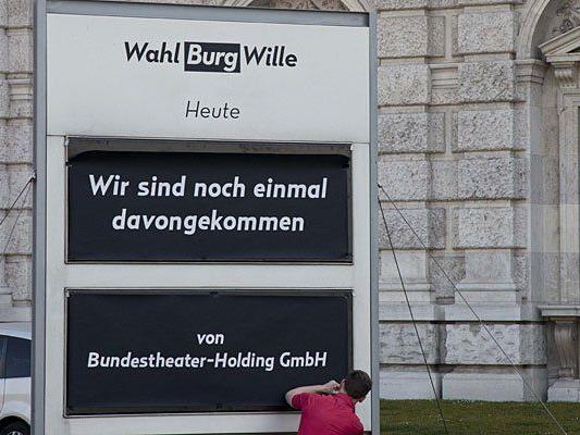 """Der niederösterreichische Künstler """"donhofer."""" bringt eine falsche Programmankündigung als Protestaktion vor dem Burgtheater an"""