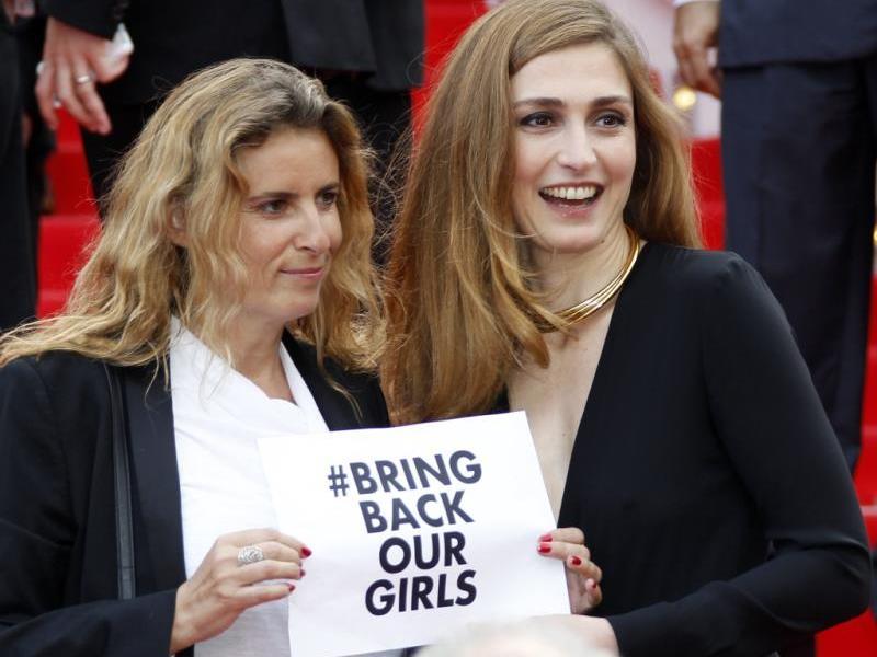 Die Französische Regisseurin Lisa Azuelos (l) and Schauspielerin Julie Gayet (r) mit dem Schriftzug '# Bring Back Our Girls'.