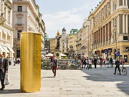 Eine goldene Säule am Graben spuckt für Passanten Euromünzen aus.