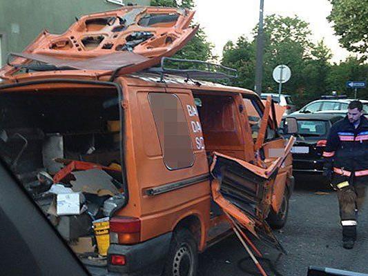 Einsatzkräfte beim beschädigten Auto an der Unglücksstelle in Wien-Favoriten