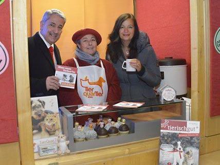Umweltstadträtin Ulli Sima mit Bezirksvorsteher Ernst Nevrivy und einer freiwilligen Helferin beim Charity-Punschstand für das TierQuarTier Wien.