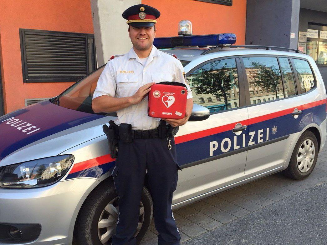 Inspektor M. hält stolz einen lebensrettenden Defibrillator in der Hand.