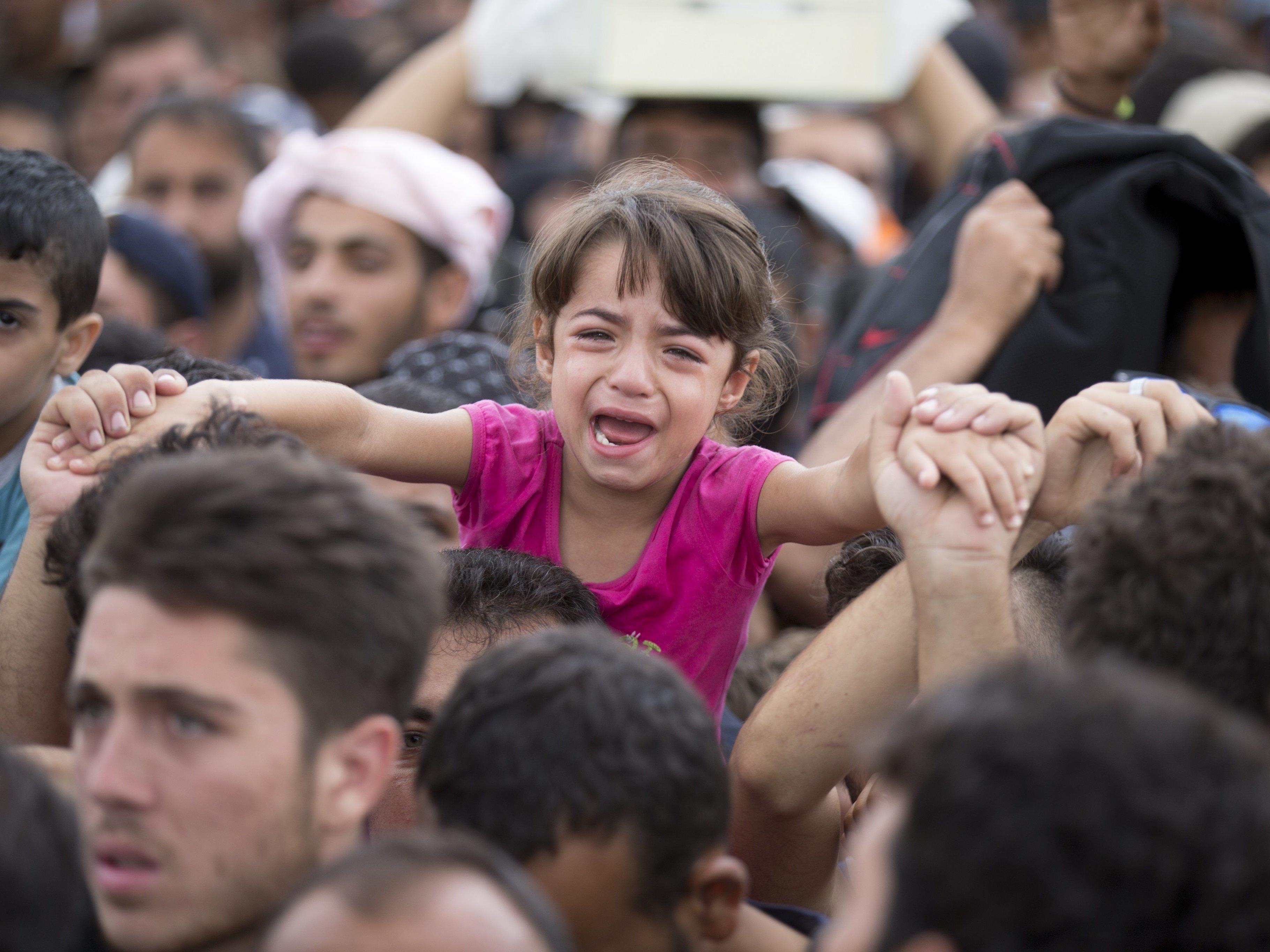 Völlig erschöpfte Flüchtlinge an der Grenze Österreichs