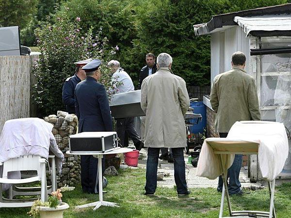Die Ermittler bei der kriminalpolizeilichen Untersuchung im Garten des Hauses, in dem die Leichen gefunden wurden