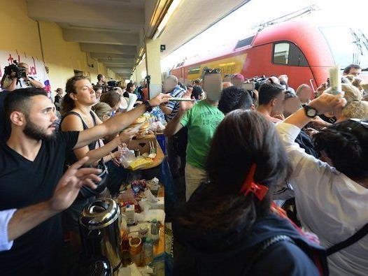 Helfer verteilen Nahrung, Getränke und Hygieneartikel an Flüchtlinge am Wiener Westbahnhof
