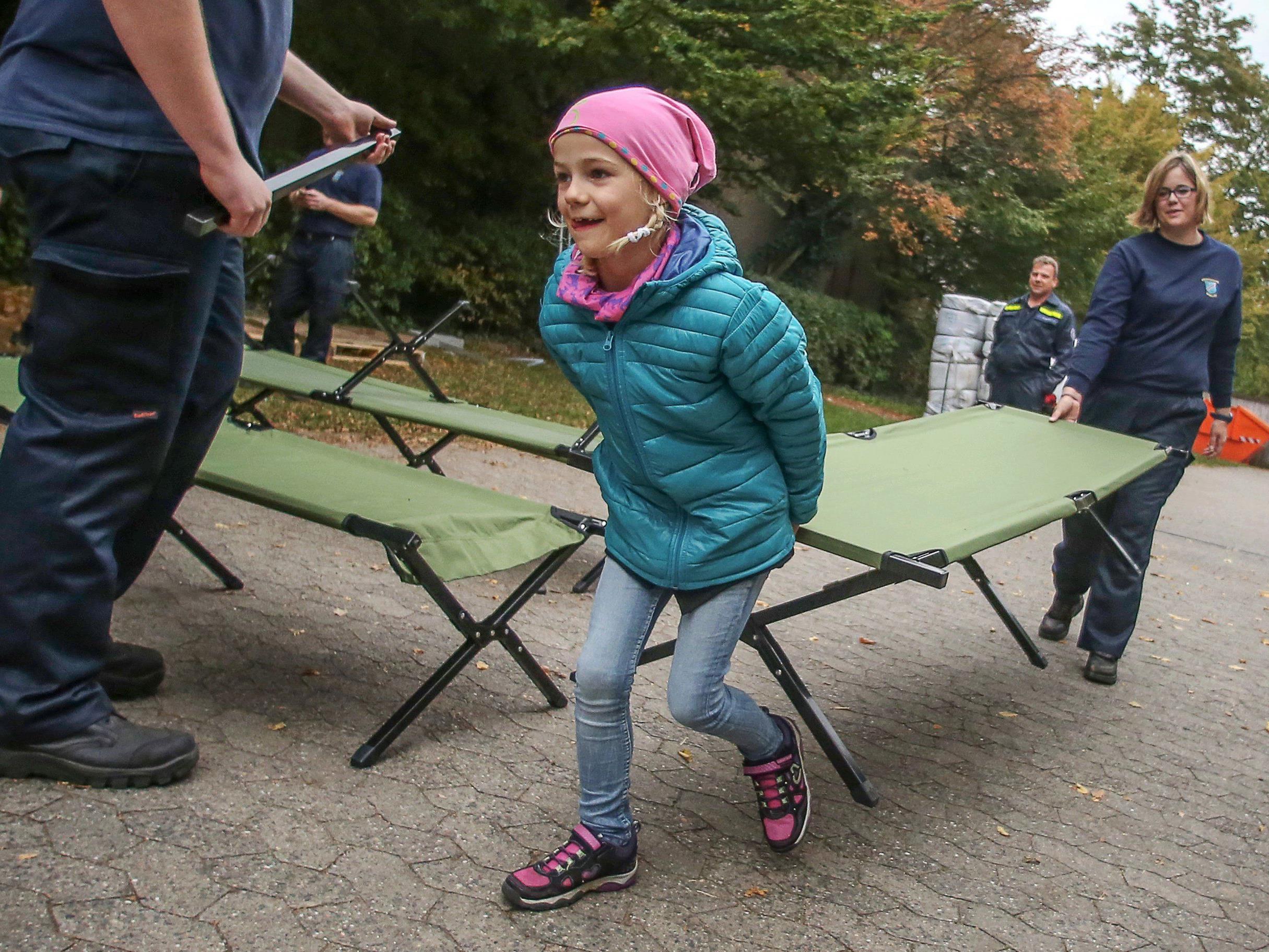 Ein kleines Mädchen hilft beim Aufbau der Flüchtlingsquartiere.