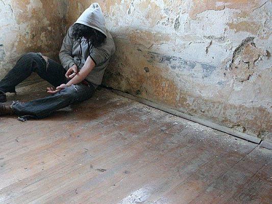 Ein junger Mann verabreicht sich mit einer Spritze Heroin (Gestellte Szene)
