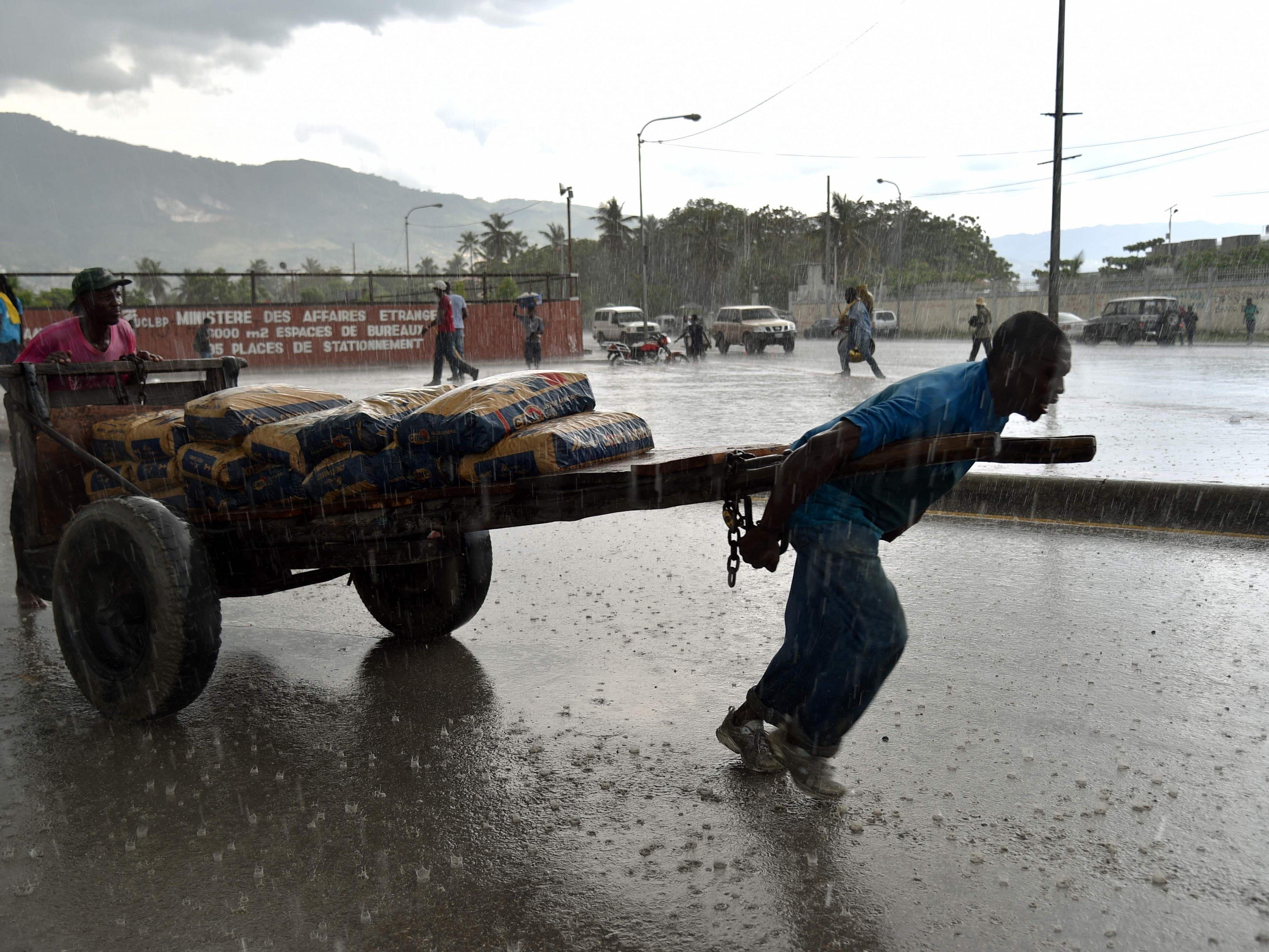 Ein Mann zieht vor dem Parlament in Port-au-Prince einen Karren mit Zement durch den Regen