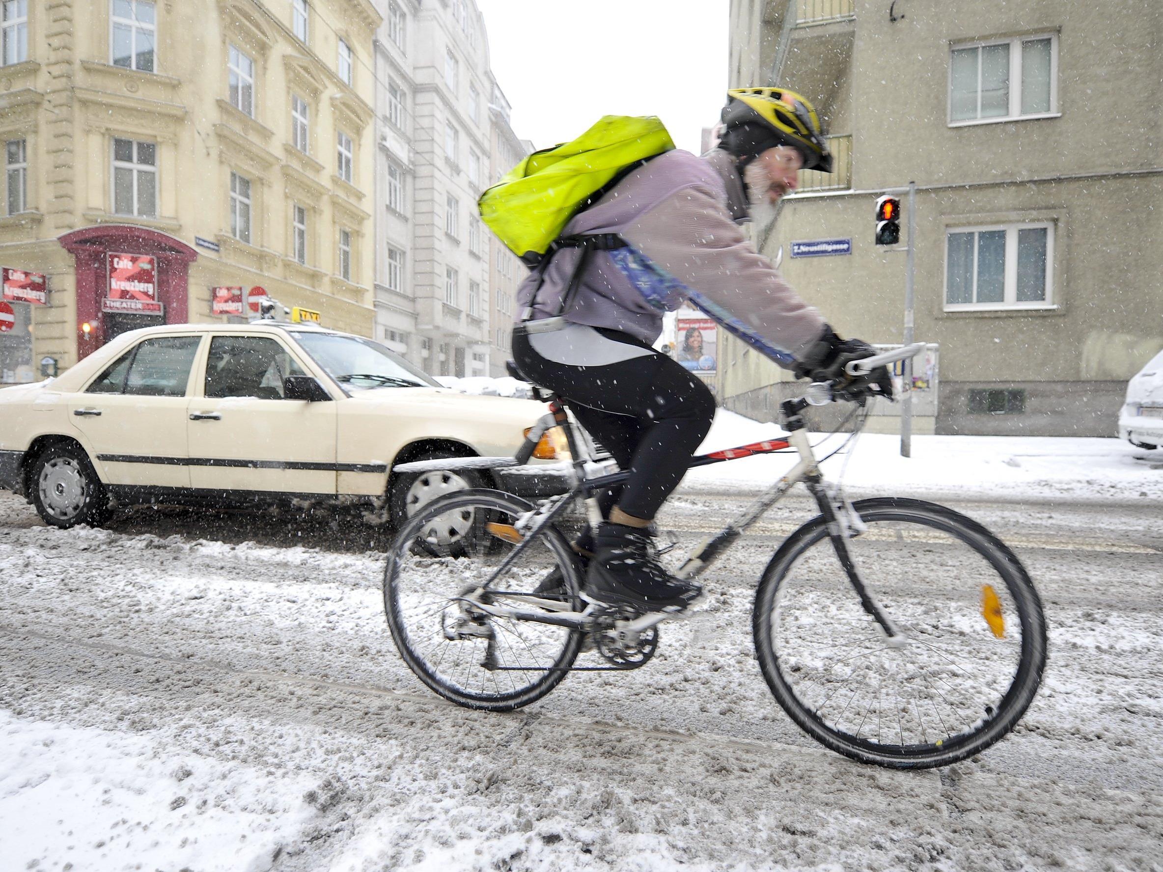 Ein Wiener Fahrradbote kämpft sich durch den Schnee.