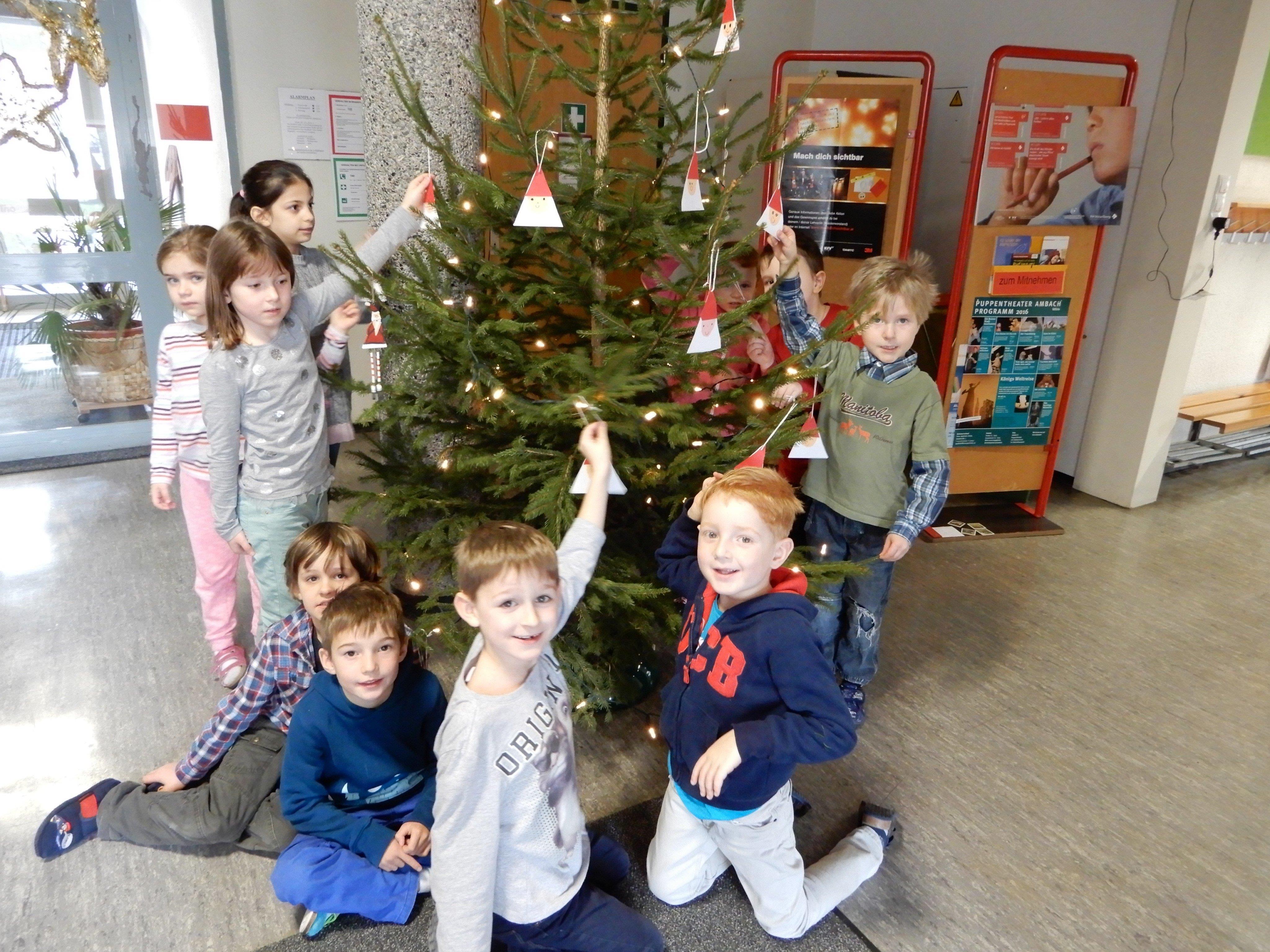 Die Kinder der 1 a VS Leopold schmücken ihren Weihnachtsbaum im Schulgang mit ihren neuen Anhängern noch fertig.