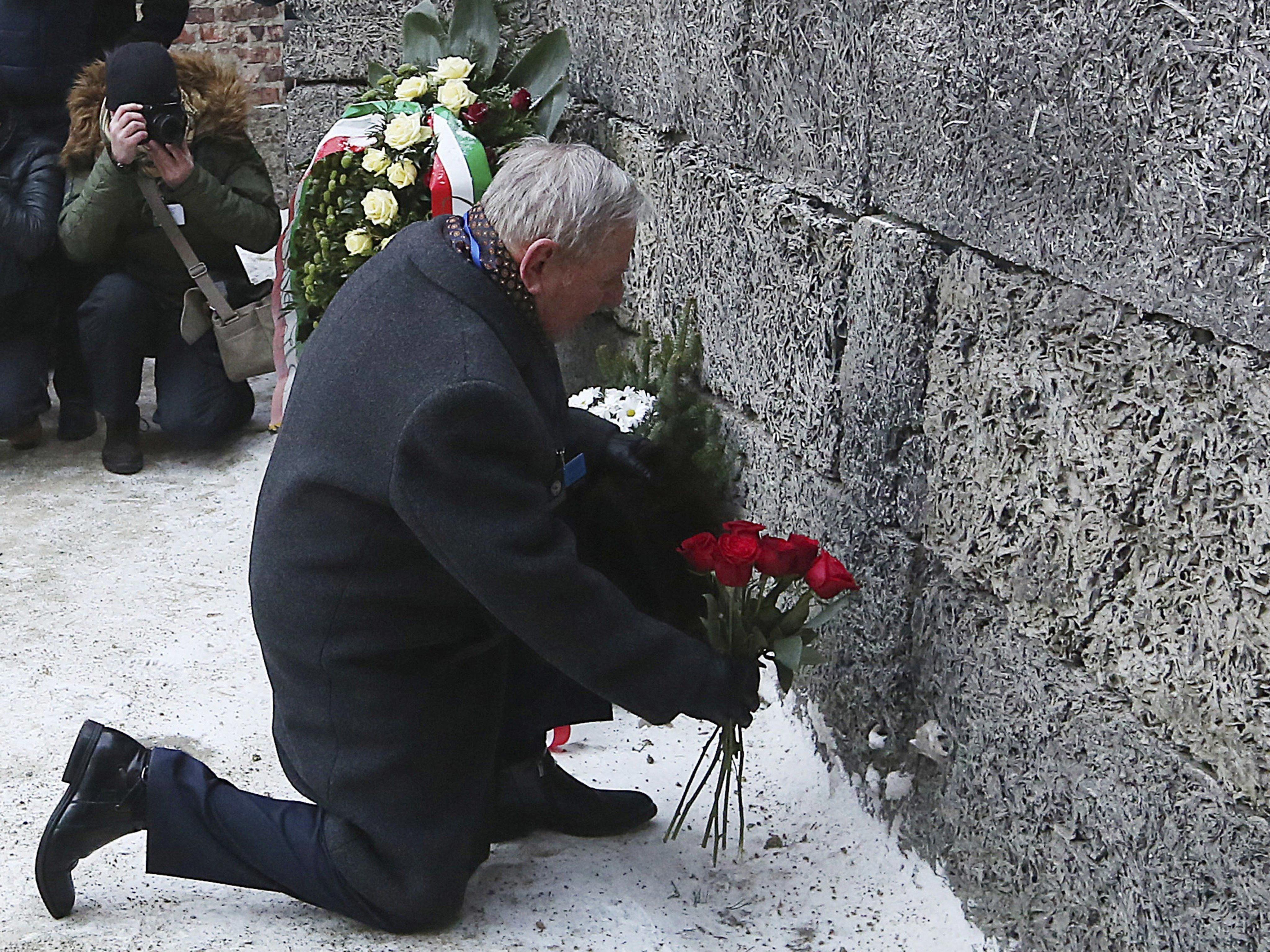 Ein Auschwitz-Überlebender legt Blumen nieder.
