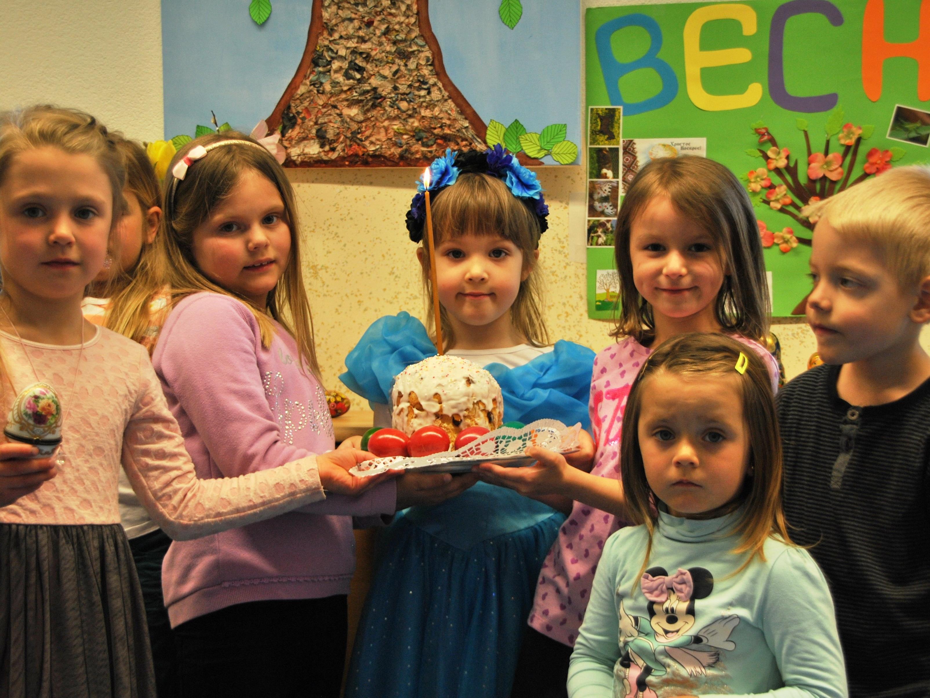 Kinder vom russischen Kinderclub mit dem Osterkuchen.
