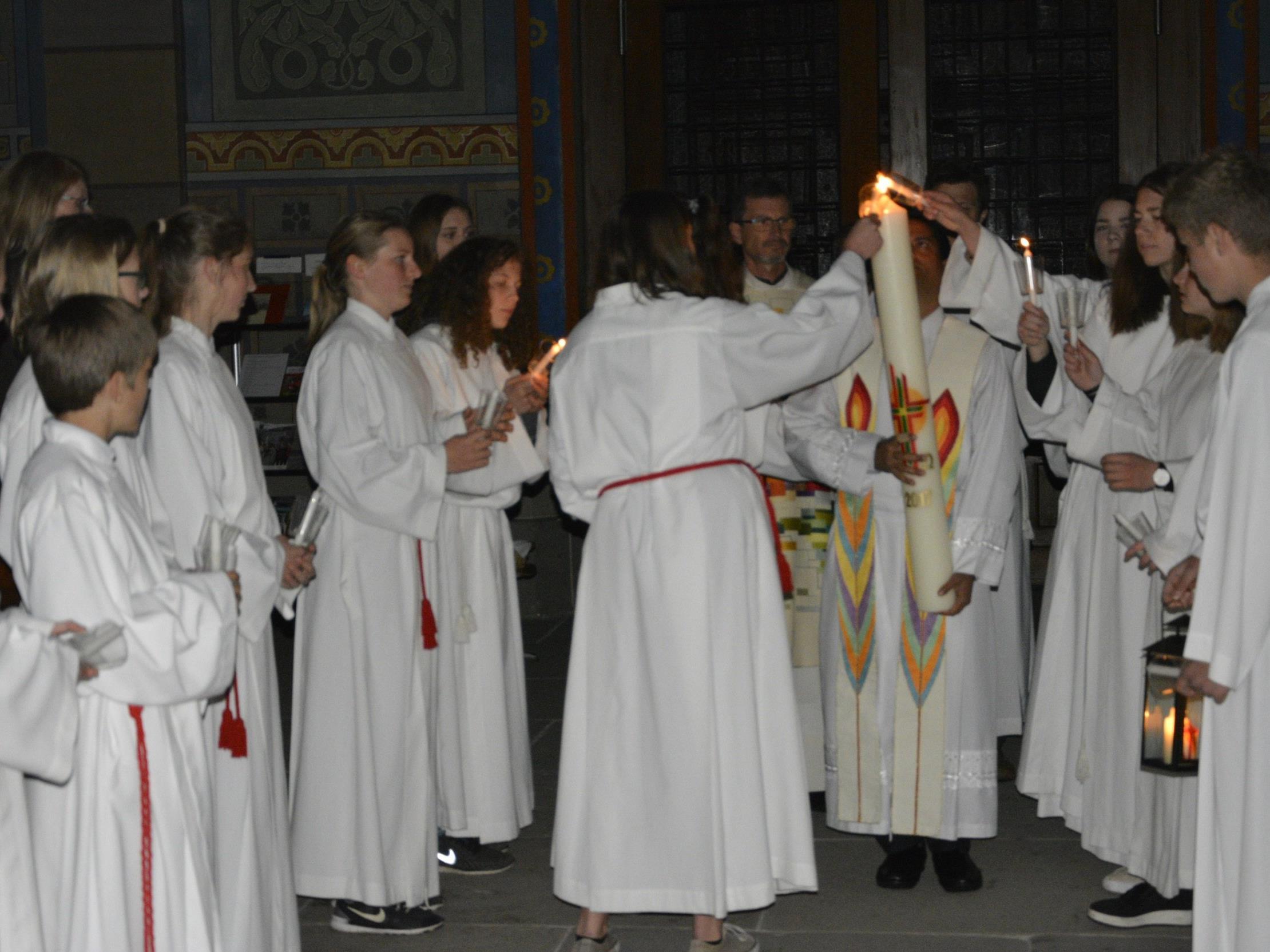Die Osterkerze wird entzündet und anschließend in die Kirche getragen.