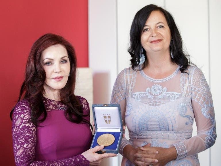 """Umweltstadträtin Ulli Sima (R) überreicht Priscilla Presley die """"Stadt-Wien-Plakette in Gold""""."""